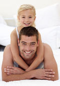 Father and daughter playing in bed — Stockfoto