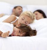 Niño sonriendo en wile cama su familia dormir — Foto de Stock