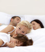 Little girl smiling wile her parents and brother sleep — Stock Photo