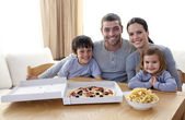 Family eating pizza and fries at home — Stock Photo