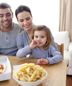 Little girl eating fries and pizza at home — Stock Photo