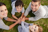 Parents and children lying on garden — Stock Photo