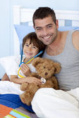 Father and son playing doctors in bed — Stock Photo