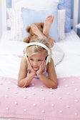 Little girl lying in bed listening to the music — Stock Photo