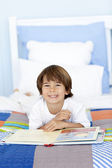 Smiling little boy reading in bed — Stock Photo