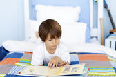 Little boy reading in bed — Stock Photo
