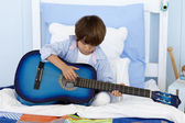 Little boy playing guitar in bed — Stock Photo