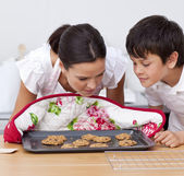 Mother and son smelling home-made biscuits — Stock Photo