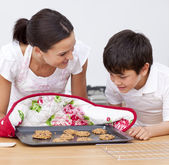 Mother and son looking at home-made biscuits — Stock Photo