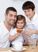 Father and children eating biscuits with milk — Stockfoto