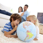 Children playing with a terrestrial globe in living-room — Stock Photo