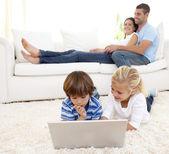使用一台笔记本电脑和父母躺在沙发上的儿童 — 图库照片