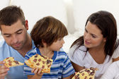 Prents and son eating pizza in living-room — Stock Photo