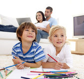 Children painting in living-room and parents on sofa — Stock Photo