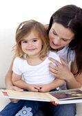 读一本书和她母亲的小女孩 — 图库照片