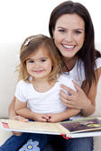Smiling mother and daughter reading a book — Stock Photo