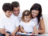 Portrait of a lovely family reading a book — Stock Photo