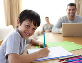 Boy painting and parents working at home — Stock Photo