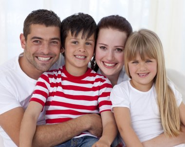 Portrait of happy family sitting on sofa together