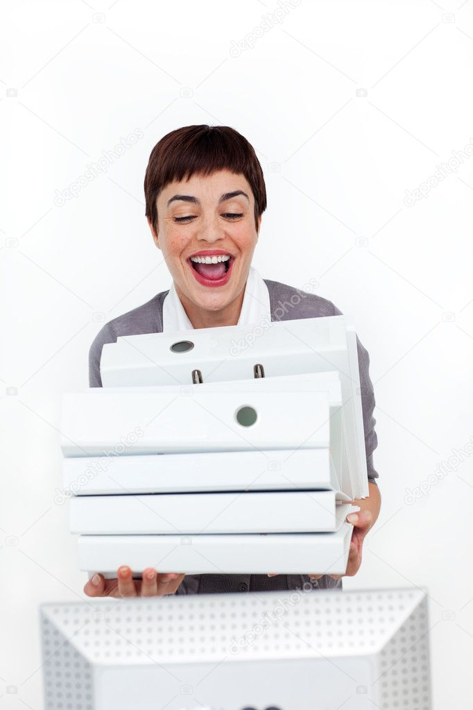 Radiant businesswoman putting a pile of folders on a desk against a white background — Stock Photo #10290396