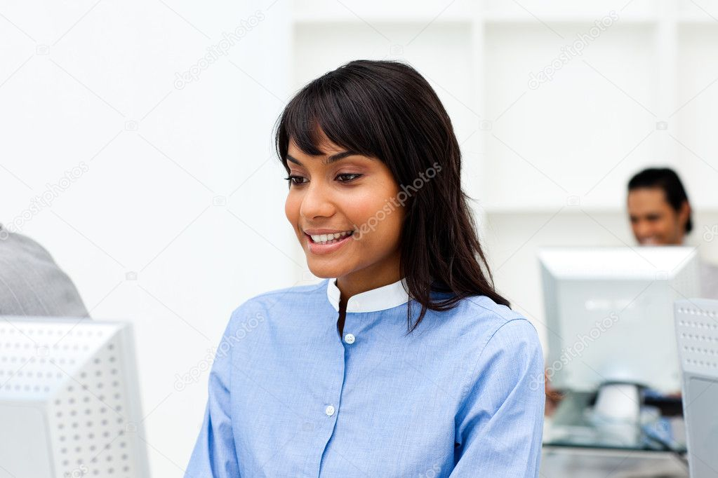Charming ethnic businesswoman working at a computer in the office — Stock Photo #10290470