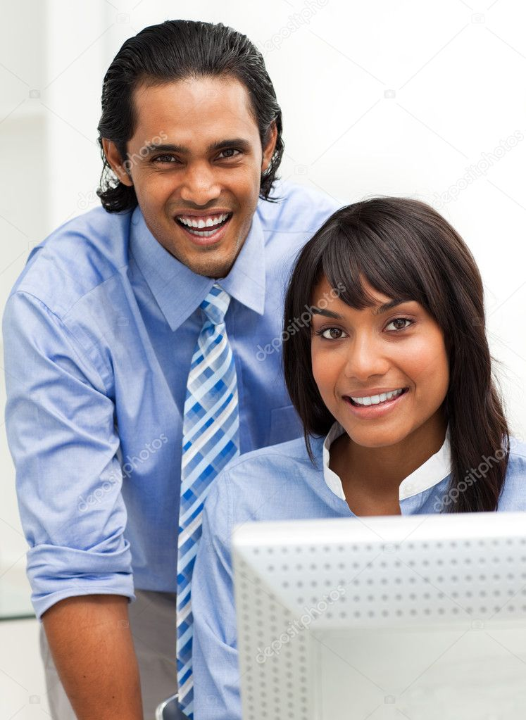 Business partners working together at a computer smiling at the camera — Stock Photo #10290481