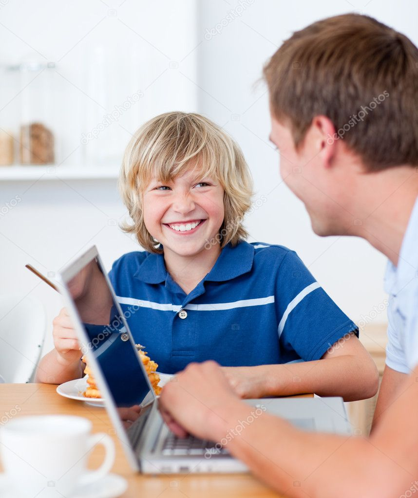 Smiling boy having breakfast while his father using a laptop in the kitchen  Stock Photo #10290984
