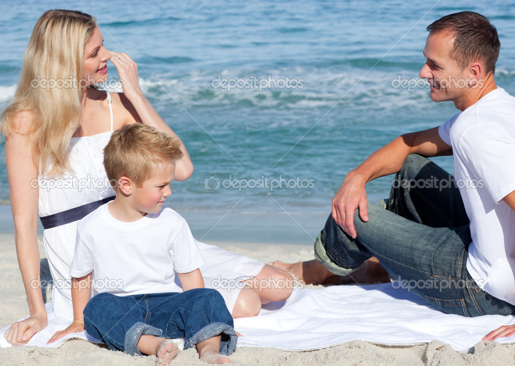 Smiling parents with their son sitting on the sand at the beach — Stock Photo #10292197