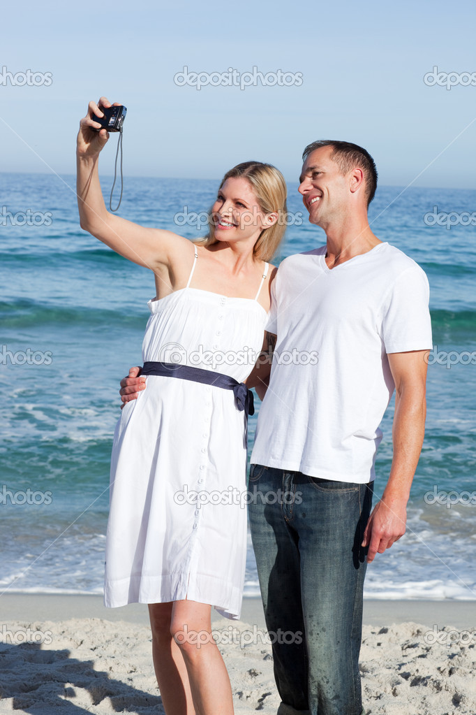 Enamored couple taking a photography at the beach — Stock Photo #10292201
