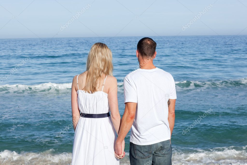 Enamored couple holding hands at the shore line at the beach  Stock Photo #10292204