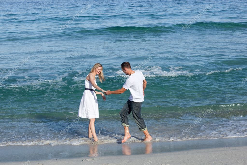 Loving couple having fun at the shore line at the beach  Stock Photo #10292205