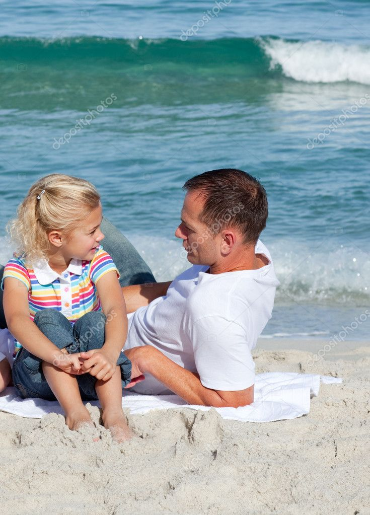 Adorable little girl and her father sitting on the sand at the beach — Stock Photo #10292217