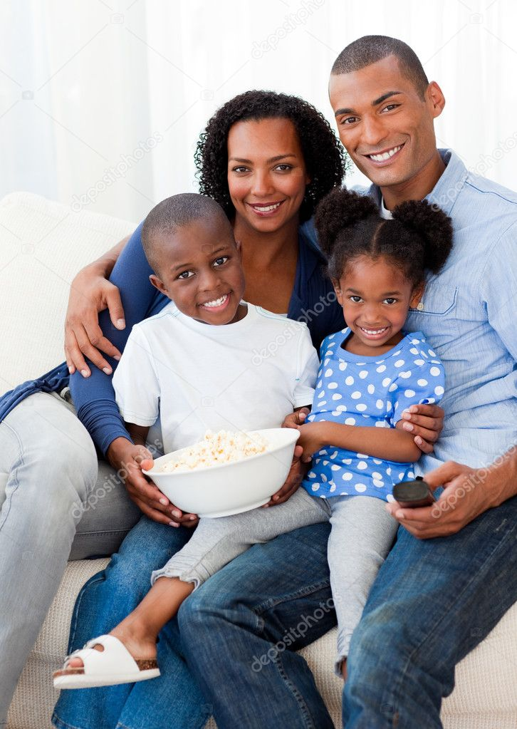 Portrait of a family eating popcorn and watching TV on the sofa — Stock Photo #10292989