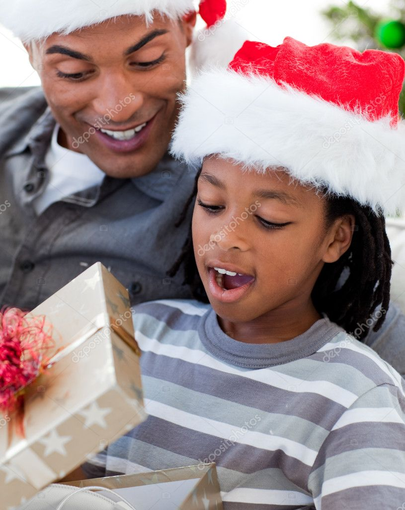 Portrait of a happy Afro-American father and son opening a Christmas gift — Stock Photo #10293276