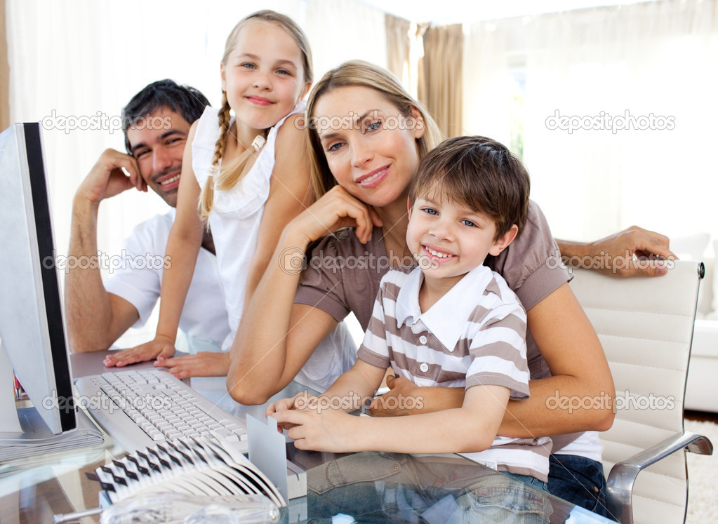 Attentive parents and their children using a computer at home — Stock Photo #10293474