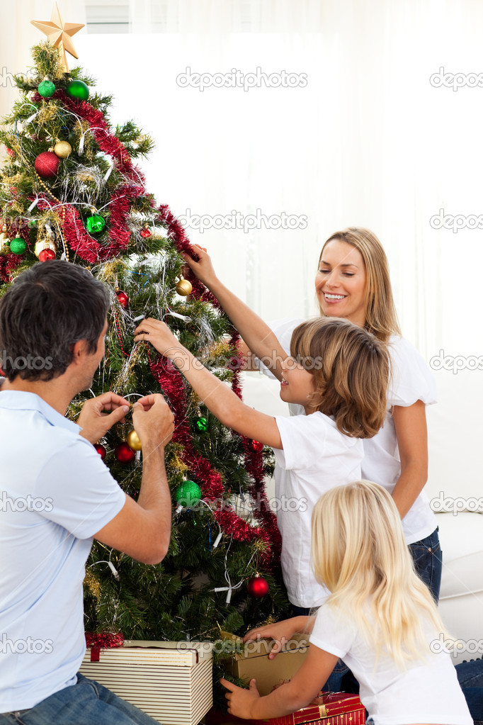 Joyful family decorating Christmas tree at home — Stock Photo #10293485