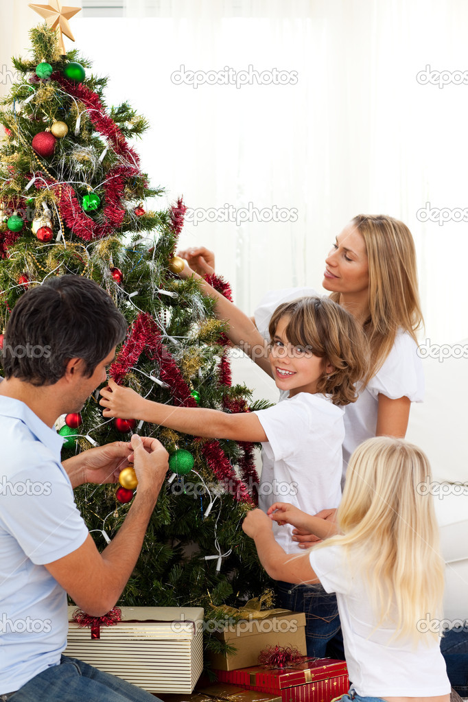 Happy family decorating Christmas tree at home — Stock Photo #10293486