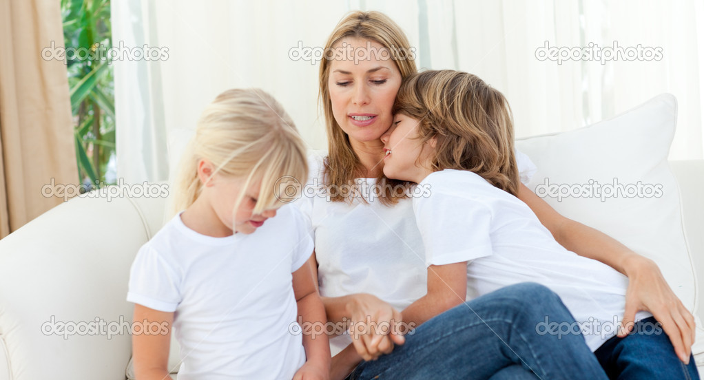 Blond mother having fun with her children sitting on sofa  Stock Photo #10293525