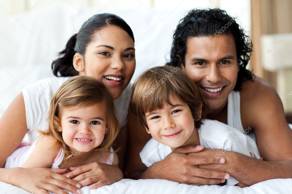 Happy family smiling at the camera in the bedroom  Stock Photo #10293689
