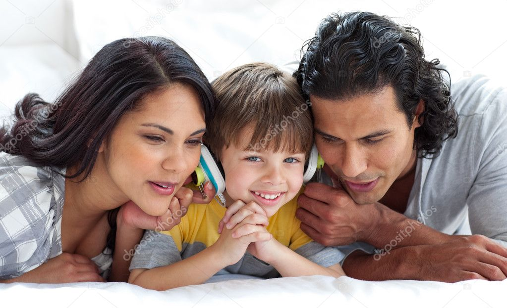 Joyful parents listening to music with their son on a bed  Stock Photo #10293757