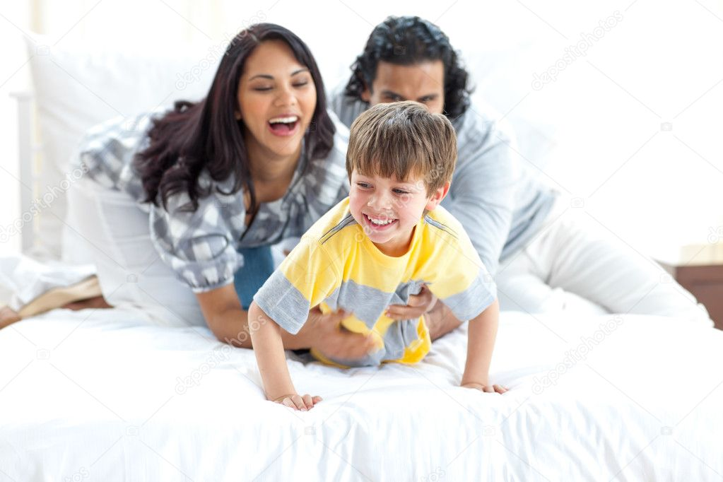 Jolly parents playing with their little boy on a bed — Stock Photo #10293758
