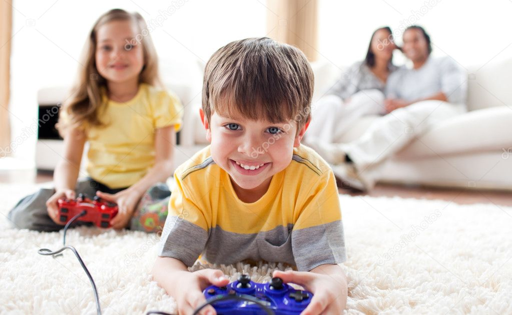 Cute little boy playing video game with his sister lying on the floor — Stock Photo #10293928