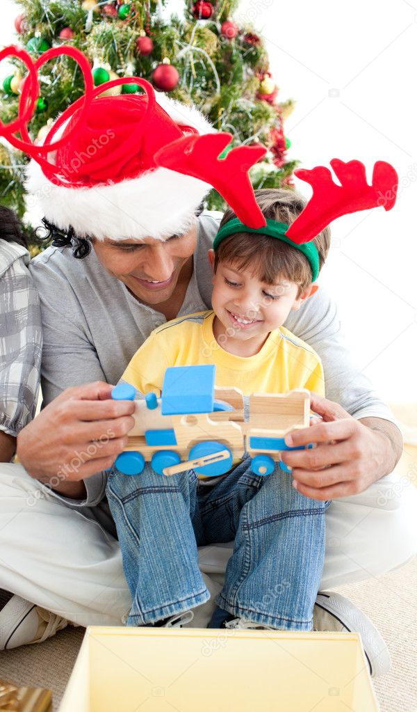 Happy child playing with a train with his father at Christmas — Stock Photo #10294009