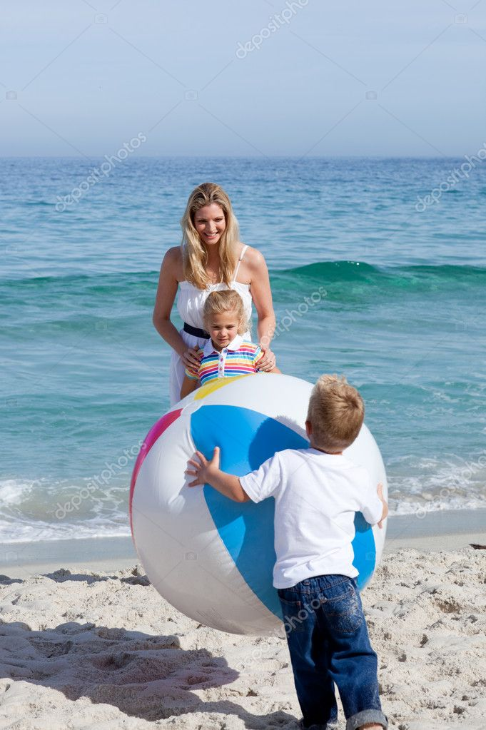 Caring mother and her children playing with a ball at the beach — Foto Stock #10294097