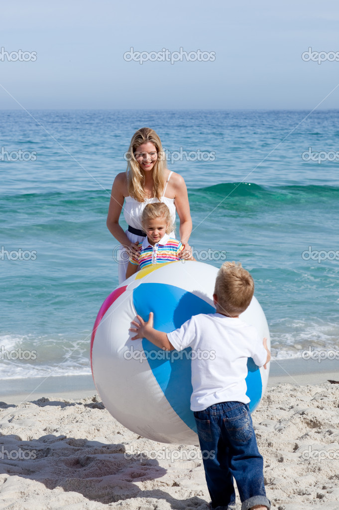 Caring mother and her children playing with a ball at the beach — Stockfoto #10294097