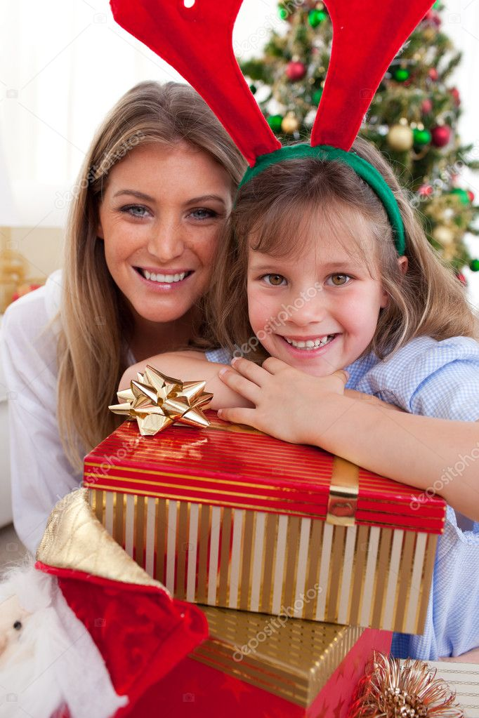 Portrait of a mother and her daughter holding Christmas presents in the living-room — Stock Photo #10294740