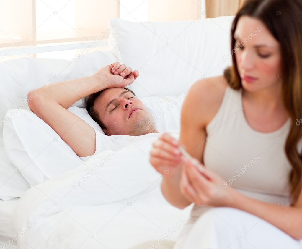 Concerned woman taking her sick husband's temperature in their bedroom — Stock Photo #10294796