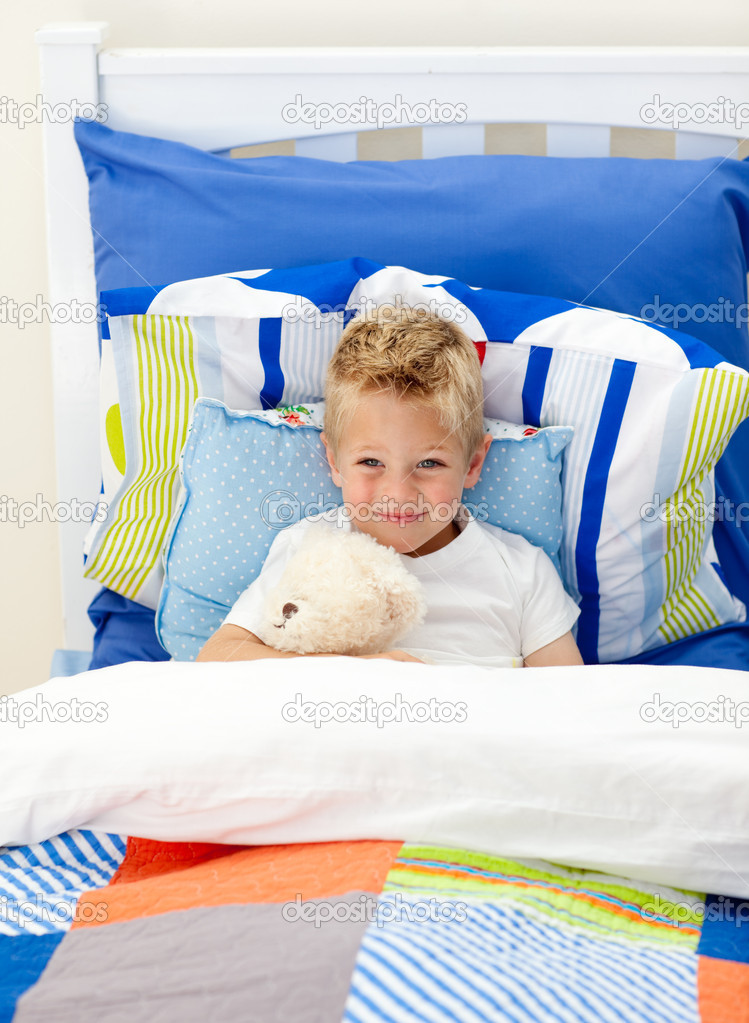 Adorable little boy lying in bed with a teddy bear — Stock Photo #10294930