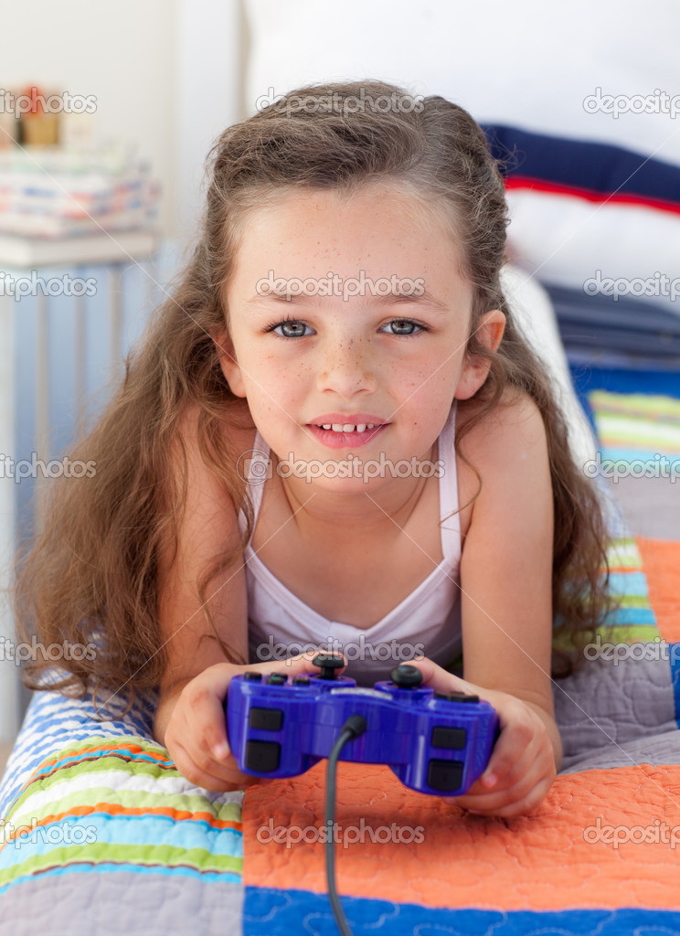 Little girl playing video games and lying on bed — Stock Photo #10295373