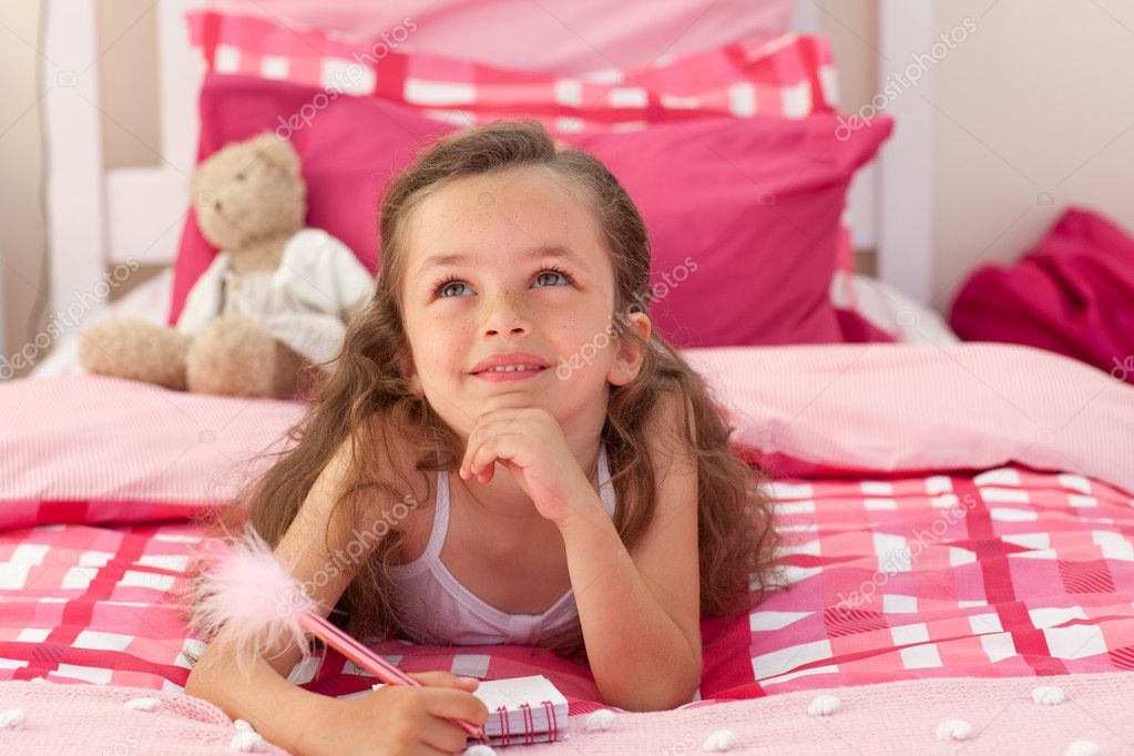Smiling girl writing and lying on bed — Stock Photo #10295385